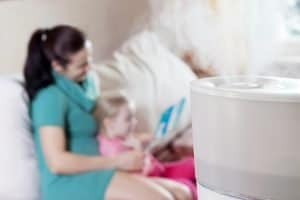 Mother Reading Story To Daughter With Humidifier On